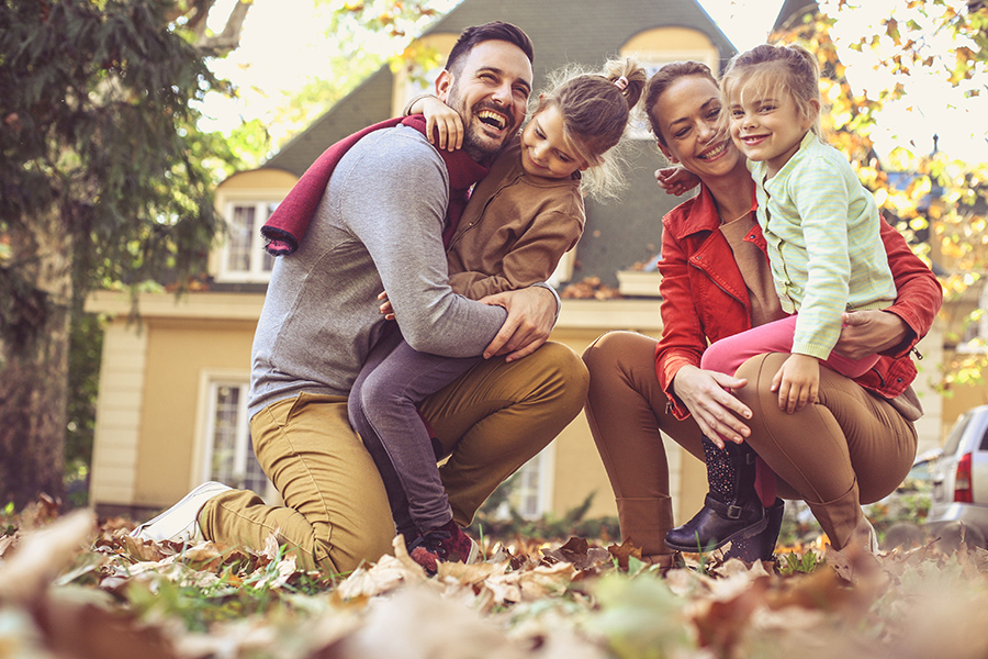 Personal Insurance - Family Having Fun Outside Their Home While Playing in Leaves in the Fall